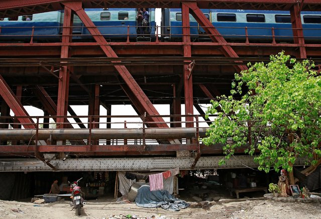 A passenger train makes its way over a bridge above a makeshift cinema in the old quarters of Delhi, India May 25, 2016. (Photo by Cathal McNaughton/Reuters)