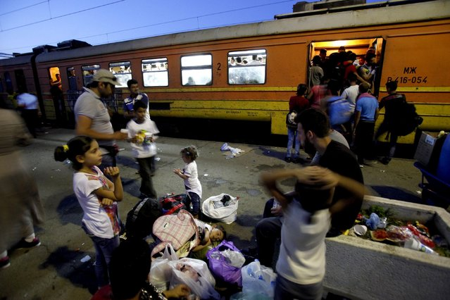 In this photo taken on Thursday, July 23, 2015 migrants board a train to Serbia at the railway station in the southern Macedonian town of Gevgelija. (Photo by Boris Grdanoski/AP Photo)