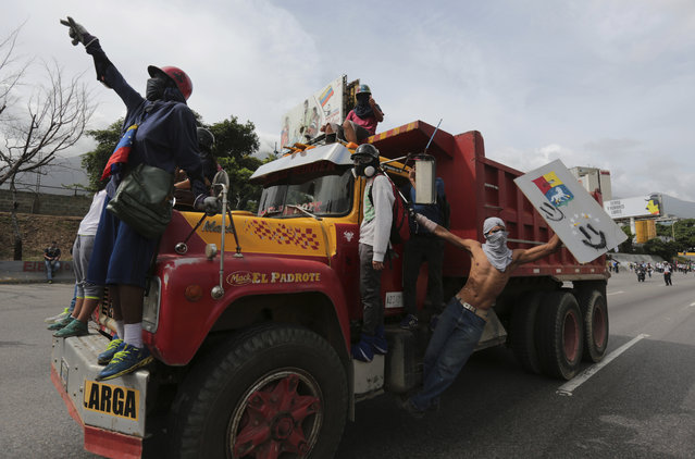 Anti-government protesters take over a cargo truck as they clash with security forces blocking their mach from reaching the National Electoral Council headquarters in Caracas, Venezuela, Wednesday, May 24, 2017. Demonstrators contend Venezuelan President Nicolas Maduro's government is quickly becoming a full-fledged authoritarian regime, and that his call to rewrite the constitution is one more attempt to consolidate his power. They are also decrying Venezuela's triple-digit inflation, soaring crime and vast food shortages. (Photo by Fernando Llano/AP Photo)