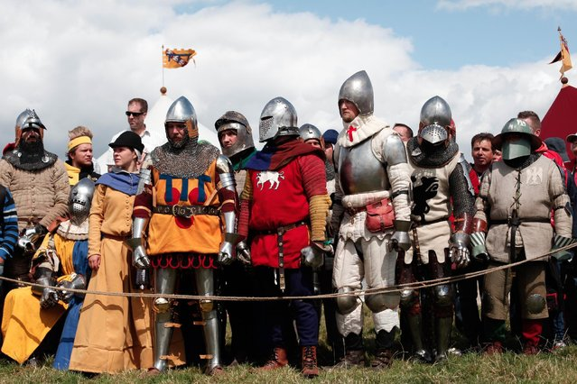 People dressed with Medieval garbs wait to see a reenactment of a tournament of knights fight, in Agincourt, northern France, Saturday, July 25, 2015. (Photo by Thibault Camus/AP Photo)