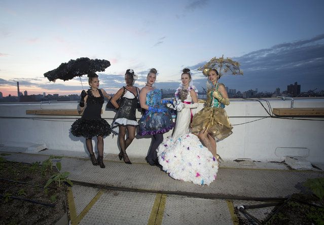 """Models take part in the """"Trashion"""" fashion show on the roof of a building in the Brooklyn Navy Yard in the Brooklyn borough of New York May 31, 2014. The show featured designers who used recycled items such as coffee filters, tissue paper, grain sacks and window screens. (Photo by Carlo Allegri/Reuters)"""