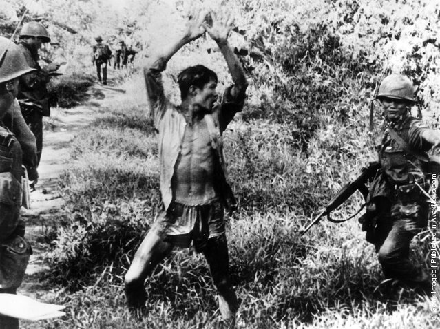 1967: A Viet Cong suspect holds his hands up after a Vietnamese Ranger from the 21st Vietnam Infantry Division routed him from his hiding place