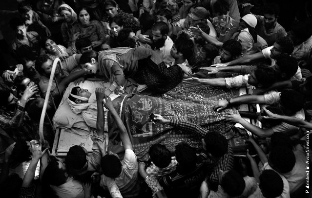 In this Sept. 6, 2010 file photo, a sister of Feroz Ahmad, alias Showkat, who was killed by forces, wails as she clings to the bed carrying the body of her brother during his funeral in Pattan, some 35 kilometers (22 miles) north of Srinagar, India. Associated Press photographer Altaf Qadri was awarded the 1st prize in the the People in the News singles category at the 2011 World Press Photo awards