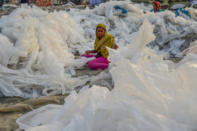 A labourer arranges plastic bags used to carry industrial chemicals to dry next to the Buriganga river in Dhaka on November 21, 2019. (Photo by Munir Uz Zaman/AFP Photo)
