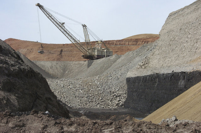 In this April 4, 2013, file photo, a dragline excavator moves rocks above a coal seam at the Spring Creek Mine in Decker, Mont. President Donald Trump says withdrawing from a global climate change agreement will boost the U.S. economy but existing market forces have had far more of an effect on the fossil fuel industries than climate regulations. For at least three years now, the coal industry has been reeling from growing competition from natural gas, wind and solar power. (Photo by Matthew Brown/AP Photo)