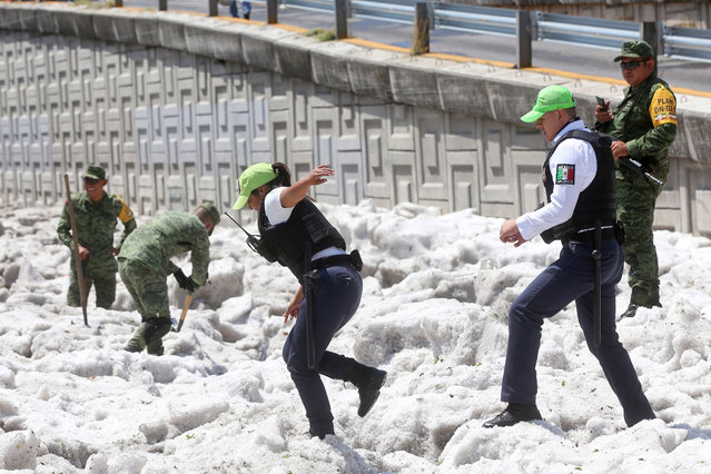 Security forces and soldiers try to clear away ice after a heavy storm of rain and hail which affected some areas of the city in Guadalajara, Mexico on June 30, 2019. Photo by Fernando Carranza/Reuters/Todos los Derechos Reservados)