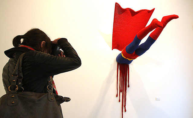 """A visitor photographs the knitted sculpture """"Superman"""" by Patricia Waller, featuring the comic book character meeting death by his own superhuman ability to fly, in the """"Broken Heroes"""" exhibition at the Deschler Gallery in Berlin, Germany. The exhibition of hand-crocheted comic, puppet and cartoon figures shows icons of pop culture in various unfortunate states"""