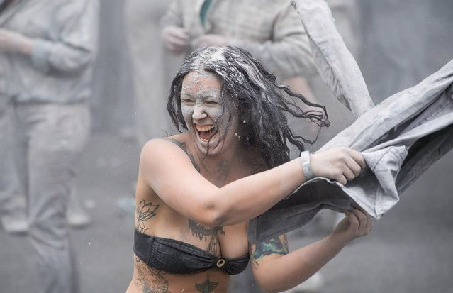 """Prostestors looking like Zombies take off their grey clothes during an arts performance called """"1000 Gestalten"""" demonstration prior the upcoming G20 summit in Hamburg, northern Germany, 05 July 2017. (Photo by Lukas Barth-Tuttas/EPA)"""