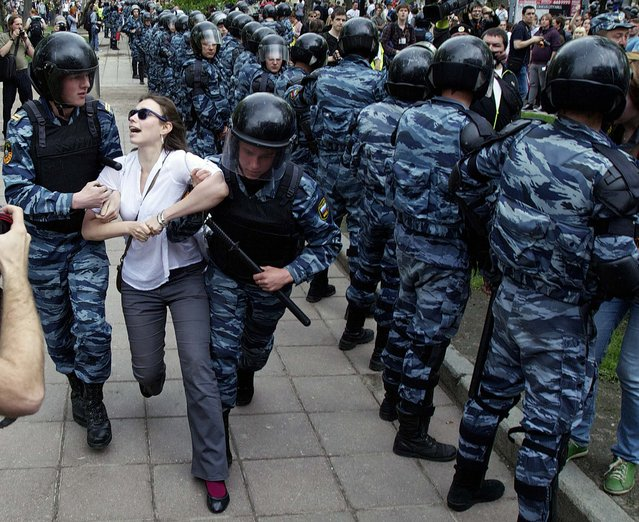 Police detain a woman after they broke up protesters gathering in downtown Moscow shortly before Vladimir Putin's inauguration on May 7, 2012
