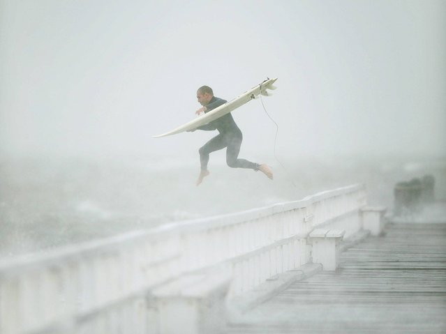 A surfer jumps off the pier into Port Phillip Bay to take advantage of the waves as a storm lashes the Melbourne area on June 24, 2014. (Photo by Mal Fairclough/AFP Photo)