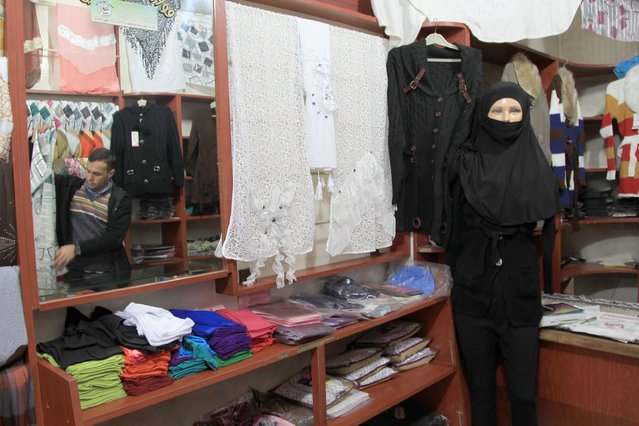 A clothes vendor arranges items near a mannequin dressed in a traditional niqab inside a shop in Aleppo January 22, 2015. (Photo by Jalal Al-Mamo/Reuters)
