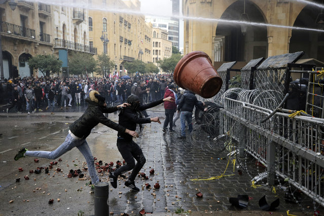 Anti-government demonstrators clash with riot police at a road leading to the parliament building in Beirut, Lebanon, Saturday, January 18, 2020. Riot police fired tears gas and sprayed protesters with water cannons near parliament building to disperse thousands of people after riots broke out during a march against the ruling elite amid a severe economic crisis. (Photo by Hassan Ammar/AP Photo)