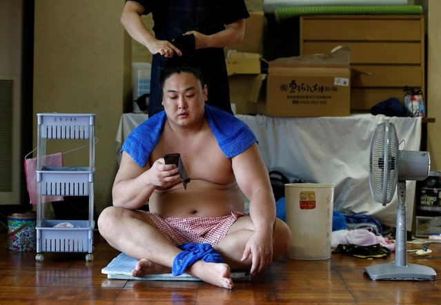 Mongolian-born sumo wrestler Kyokushuho has his hair fixed after a training session in Nagoya, Japan on July 18, 2017. (Photo by Issei Kato/Reuters)