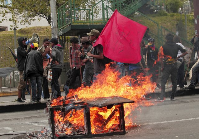 Demonstrators stand behind a burning blockade on a street during a protest in Quito, Ecuador, August 13, 2015. Dozens of workers, union leaders and indigenous Ecuadorians on Thursday blocked roads to Quito with branches and rocks to protest President Rafael Correa's plans to hike taxes and reform the constitution to allow indefinite presidential re-election. (Photo by Guillermo Granja/Reuters)
