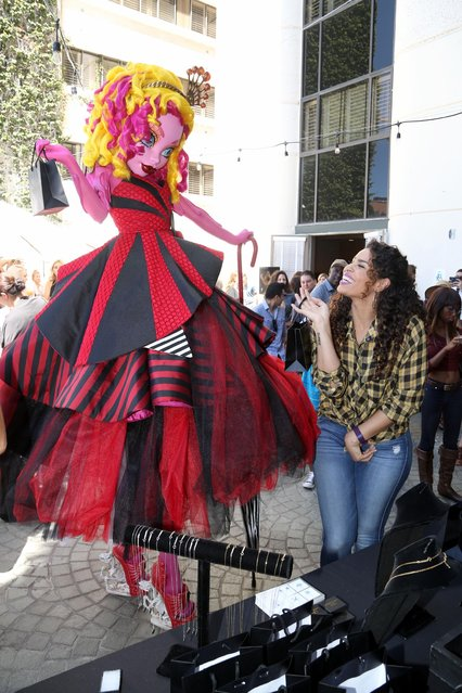 Jordin Sparks and Gooliope, the tallest Monster High character, try on fierce and fabulous jewelry at KIIS-FM's Teen Choice Gifting Suite on Fri., August 14, 2014, in Los Angeles. (Photo by Casey Rodgers/Invision for Mattel/AP Images)