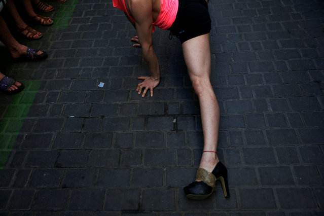 A competitor stretches before the annual race on high heels during Gay Pride celebrations in the quarter of Chueca in Madrid, Spain, June 30, 2016. (Photo by Susana Vera/Reuters)