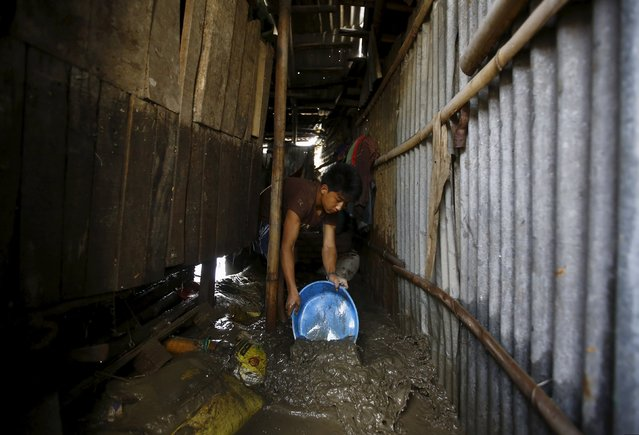 A man clears water from his shed after floodwaters caused by heavy rainfall flowing from the swollen Bagmati River entered the slum in Kathmandu, Nepal August 17, 2015. (Photo by Navesh Chitrakar/Reuters)