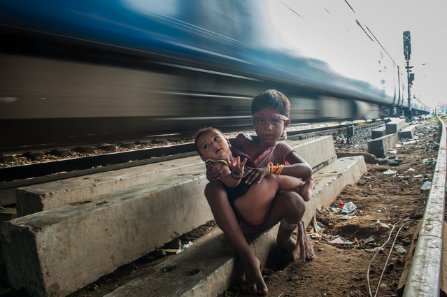 A girl holds her brother while a train passes behind them near Okhla railway station in New Delhi, India on June 29, 2016. (Photo by Shams Qari/Barcroft Images)
