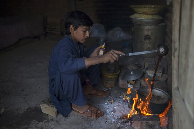 Samiullah, who says he is 14-years-old, prepares tea after finishing work at a coal mine in Choa Saidan Shah, Punjab province, May 5, 2014. (Photo by Sara Farid/Reuters)