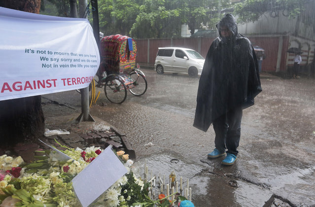 A Bangladeshi man stands in the rain and pays his respects to the victims of the attack on Holey Artisan Bakery, in Dhaka, Bangladesh, Tuesday, July 5, 2016. The attack, the worst convulsion of violence yet in the recent series of deadly attacks to hit Bangladesh, has stunned the traditionally moderate Muslim nation and raised global concerns about whether it can cope with increasingly strident Islamist militants. (Photo by AP Photo)