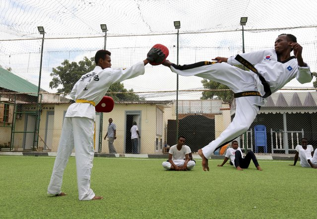 A martial arts instructor Ahmed Mohamed shows his students fighting skills at a Karate school in Somalia's capital Mogadishu, August 21, 2015. Livelihood has fairly returned to normalcy the war ravaged country after Al Qaeda-linked al Shabaab, which wants to topple the Western-backed government and impose its strict interpretation of Islam on Somalia, has been driven out of major strongholds by the African and Somali forces but continues to launch bomb and gun attacks against officials, politicians and others. (Photo by Feisal Omar/Reuters)
