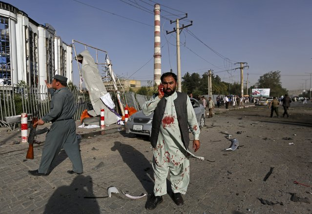 An Afghan man talks on his phone after a bomb blast in Kabul, Afghanistan August 22, 2015.  A car bomb exploded outside a private hospital in Kabul on Saturday killing one person and injuring 18 more, a senior health official said. (Photo by Mohammad Ismail/Reuters)