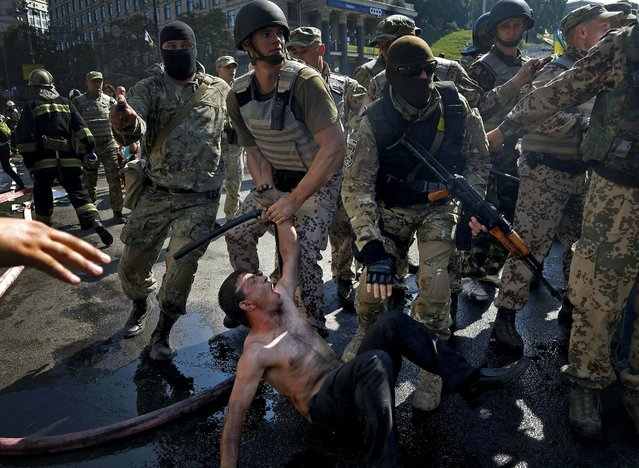 Police battalion officers detain an activist during a clash in Independence Square in Kiev, Ukraine, after  authorities attempted to dismantle barricades demonstrators had set up, on August 7, 2014. (Photo by Efrem Lukatsky/Associated Press)