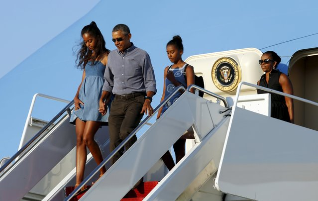 U.S. President Barack Obama holds hands with his daughter Malia as the Obama family disembark Air Force One upon their return to Washington after a two-week vacation on Martha's Vineyard August 23, 2015. (Photo by Kevin Lamarque/Reuters)