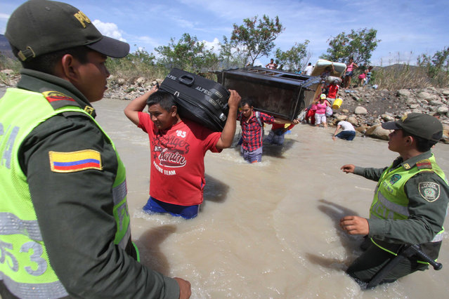 Colombian police watch people carry their household belongings across the Tachira River from Venezuela, top, to Colombia, on the border that separates San Antonio del Tachira, Venezuela from Villa del Rosario, Colombia, Tuesday, August 25, 2015, during a mass exodus of Colombians. (Photo by Eliecer Mantilla/AP Photo)