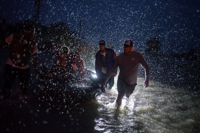Samaritans help push a boat with evacuees to high ground during a rain storm caused by Tropical Storm Harvey along Tidwell Road in east Houston, Texas, U.S. August 28, 2017. (Photo by Adrees Latif/Reuters)