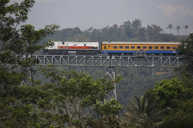 A passenger train crosses a bridge as it travels from Jakarta to Bandung near Padalarang, West Java, Indonesia August 25, 2015. Japan's prime minister has dispatched a special envoy to offer Jakarta a sweetened deal to build Indonesia's first high-speed railway, an embassy official said, in an eleventh hour move that highlights the importance of winning the multi-billion dollar project over China. (Photo by Darren Whiteside/Reuters)