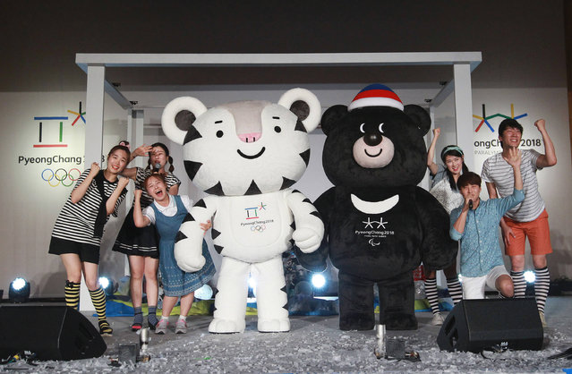 Volunteers pose with the official mascots for the 2018 PyeongChang Olympic and Paralympic Winter Games, white tiger Soohorang, left, for Olympic, and black bear Bandabi for Paralympic, during their launching ceremony at Hoeng Gye Elementary School in Pyeongchang, South Korea, Monday, July 18, 2016. The PyeongChang Organizing Committee for the 2018 Olympic and Paralympic Winter Games launched on Monday its nationwide mascot promotion tour. (Photo by Ahn Young-joon/AP Photo)