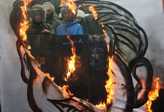 """Riot police look on past a burning banner with a representation of a composite portrait of late dictator Ferdinand Marcos and President Rodrigo Duterte, with a slogan that reads """"Marcos, Duterte, fascist"""" during a demonstration held on the 100th birthday of late dictator Ferdinand Marcos, near the Heroes Cemetery in Manila on September 11, 2017. Riot police on September 11 blocked hundreds of protesters trying to disrupt the family of the late dictator Ferdinand Marcos from celebrating his 100th birthday at the Philippines' """"Heroes Cemetery"""". (Photo by Ted Aljibe/AFP Photo)"""