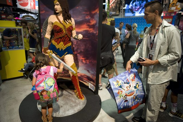 Michael Escobedo watches his daughter as she examines a statue of DC Comics character Wonder Woman made from Lego during the Preview Night before the San Diego Comic Con 2016 in San Diego, California, USA, 20 July 2016. (Photo by David Maung/EPA)
