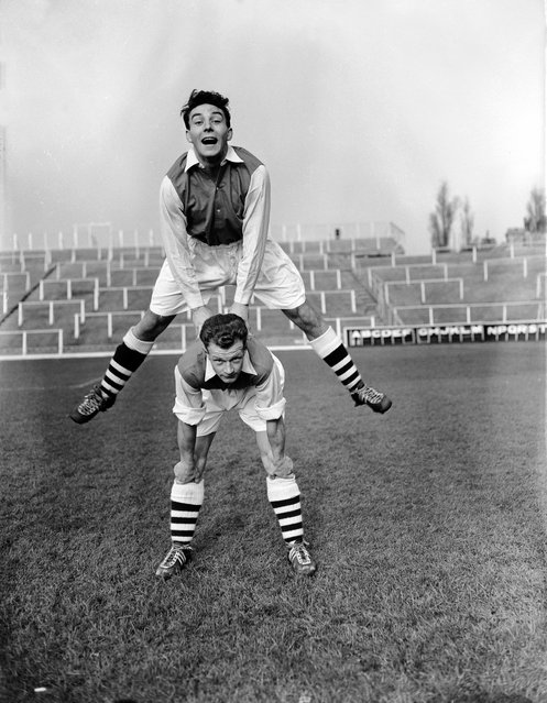 Arsenal's new signings from Leyton Orient, Vic Groves (jumping) and Stan Charlton, enjoying their first day of trraining at Arsenal's Highbury Stadium in North London, 8th November 1955. (Photo by L. Blandford)