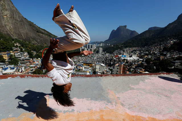 A member of the Acorda Capoeira (Awaken Capoeira) group performs on a rooftop in the Rocinha favela in Rio de Janeiro, Brazil, July 24, 2016. (Photo by Bruno Kelly/Reuters)