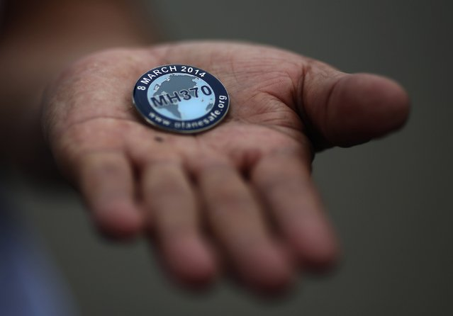 Zhang Yongli, whose daughter Zhang Qi was onboard Malaysia Airlines Flight MH370 which disappeared on March 8, 2014 shows a badge which he received from an NGO group supporting the family members of missing passengers, during an interview with Reuters in Beijing July 22, 2014. (Photo by Kim Kyung-Hoon/Reuters)