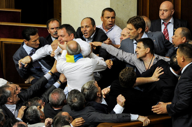 Opposition lawmakers clash with deputies of parliament's majority during a session of the Ukrainian Parliament, in Kiev, Ukraine, 24 March 2012.  The brawl broke out when deputies were controversially discussing a bill on granting Russian being the official language. (Photo by Aleksandr Svetlov/EPA)