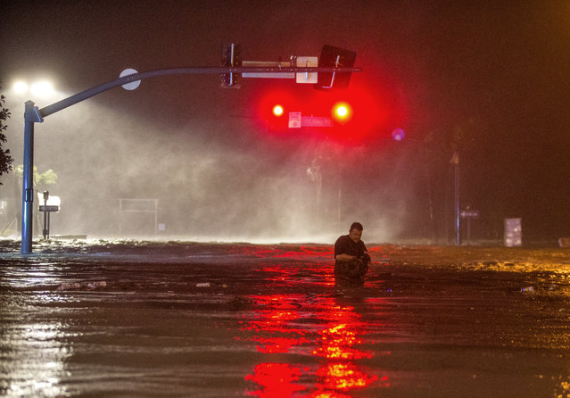 Lanny Dean, from Tulsa, Oklahoma, takes video as he wades along a flooded Beach Boulevard next to Harrahs Casino as the eye of Hurricane Nate pushes ashore in Biloxi, Mississippi October 8, 2017. Hurricane Nate flooded the parking garage and first floors of Golden Nugget, Harrahs and other casinos as it made a second landfall on the Mississippi coast as a category 1 storm. (Photo by Mark Wallheiser/Getty Images)