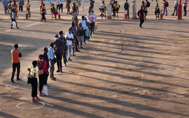 People stand in white circles to adhere to social distancing to curb the spread of the COVID-19 coronavirus as they wait for a bus at Nyabugogo bus station in Kigali, Rwanda, on May 4, 2020, the first day back from the nationwide coronavirus lockdown. People are now allowed to stay outside from 5am to 8pm and public transports have been resumed except county borders after six weeks of the lockdown. Wearing masks are still mandatory in public space. (Photo by Simon Wohlfahrt/AFP Photo)