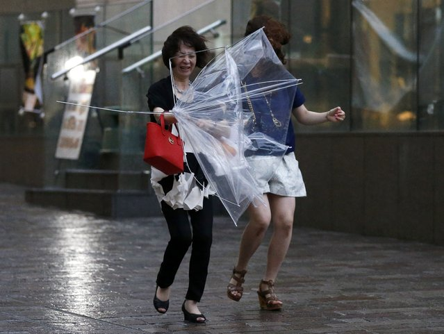 Women struggle with strong winds and rain caused by Typhoon Halong in Tokyo August 10, 2014. Typhoon Halong killed one person in Japan on Sunday and injured 33, media said, as authorities ordered 1.6 million people out of the path of the storm that battered the west of the country with heavy rain and wind. (Photo by Toru Hanai/Reuters)