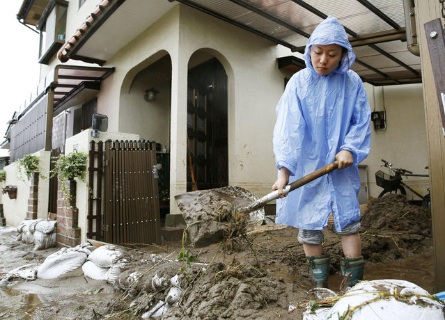 A woman clean dirt and debris caused by a flooding in Kanuma, Tochigi prefecture, north of Tokyo Thursday, September 10, 2015. (Photo by Kyodo News via AP Photo)
