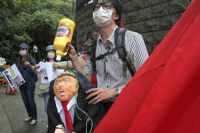 Pro-China supporters hold the effigy of U.S. President Donald Trump outside the U.S. Consulate during a protest, in Hong Kong, Saturday, May 30, 2020. President Donald Trump has announced a series of measures aimed at China as a rift between the two countries grows. He said Friday that he would withdraw funding from the World Health Organization, end Hong Kong's special trade status and suspend visas of Chinese graduate students suspected of conducting research on behalf of their government. (Photo by Kin Cheung/AP Photo)