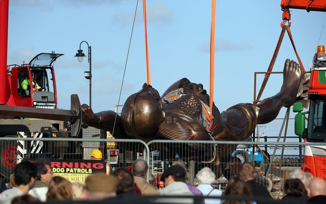 Contractors move Damien Hirst's bronze sculpture of a pregnant woman into positionl on October 16, 2012 in Ilfracombe, England. The bronze-clad, sword-wielding 65ft (20m) statue, named Verity, has been controversially given to the seaside town by the artist, on a 20-year loan and was erected by crane on the pier.  (Photo by Matt Cardy)