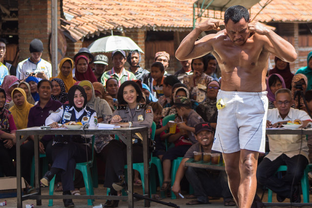 Tile factory workers take part in a contest to show their muscular strength and power in Majalengka, Indonesia on August 14, 2016. (Photo by Ed Ismail/Barcroft Images)