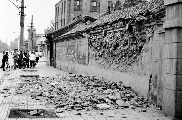 Almost an entire wall of a house in Peking lies in a heap on the sidewalk, July 31, 1976, after a severe earthquake which rocked the Chinese capital on Wednesday. (Photo by John R. Zelenik/AP Photo)