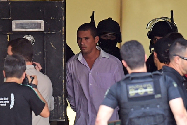 The unidentified man (C in shirt) who earlier today held hostage a hotel employee and forced him to wear an explosive-laden vest is taken out from the hotel in Brasilia on September 29, 2014. An armed man took an employee hostage at a hotel in the Brazilian capital and then appeared several times on the balcony, waving a pistol, with his handcuffed hostage wearing a jacket that appeared to contain explosives. (Photo by Evaristo Sa/AFP Photo)