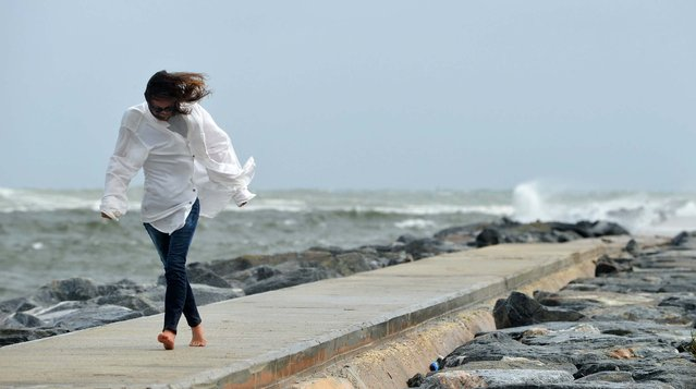 Alison Reed pushes against the wind Friday afternoon on the north jetty in Palm Beach. (Photo by Jeffrey Langlois/Palm Beach Daily News)