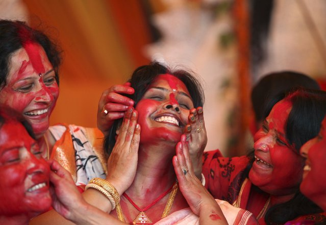 "Hindu women apply ""Sindur"", or vermillion powder, on the face of a woman during the Durga Puja festival in the northern Indian city of Chandigarh October 3, 2014. The festival is the biggest religious event for Bengali Hindus. Hindus believe that the goddess Durga symbolises power and the triumph of good over evil. (Photo by Ajay Verma/Reuters)"