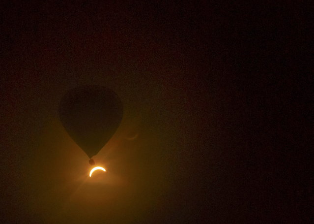 In this photo provided by Tourism Queensland, a hot air balloon floats in the air as a solar eclipse is observed near Cairns, in Queensland state, Australia, Wednesday, November 14, 2012. Starting just after dawn, the eclipse cast its 150-kilometer (95-mile) shadow in Australia's Northern Territory, crossed the northeast tip of the country and was swooping east across the South Pacific, where no islands are in its direct path. (Photo by David Barker/Tourism Queensland/AP Photo)